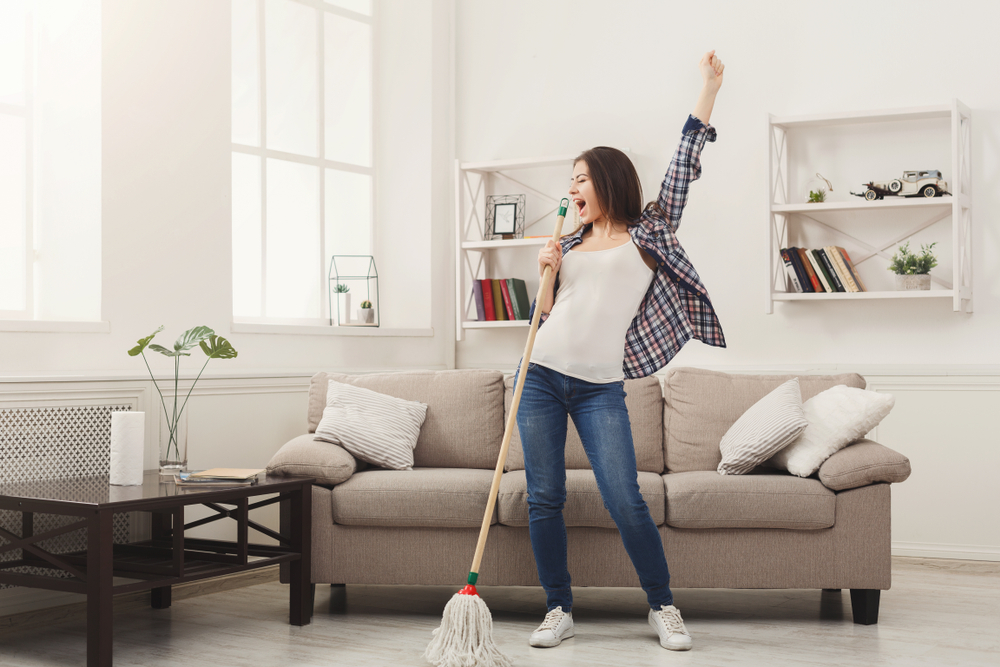 Woman with cleaning mop singing