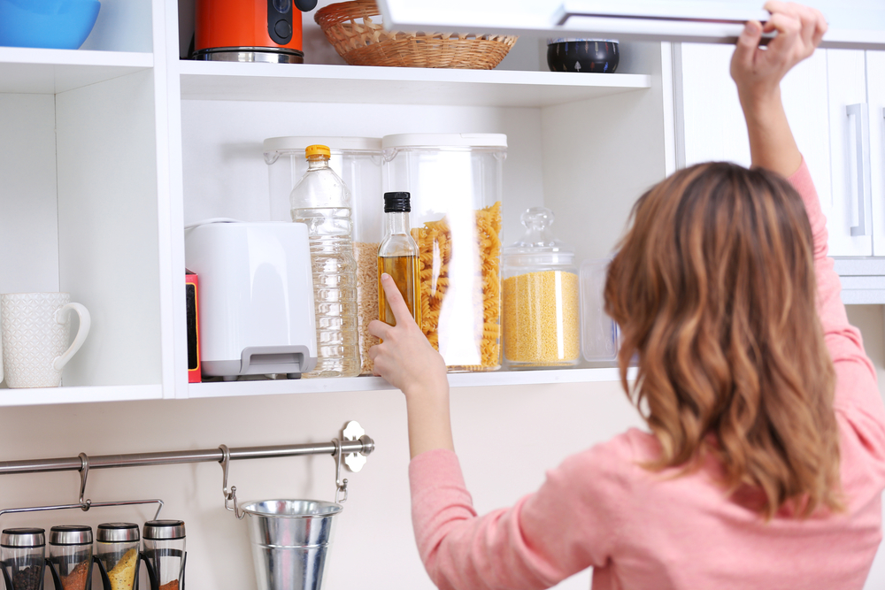 Woman tidying kitchen cupboards